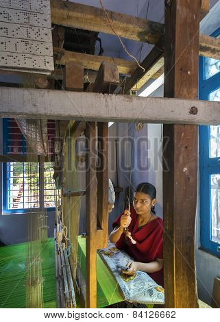 Young Woman Works Inside Home On A Hand Loom.
