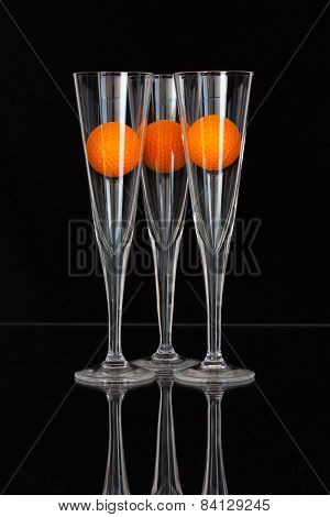 Three Glasses Of Champagne And Orange Golf Balls