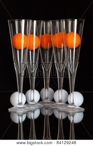 Five Glasses Of Champagne, White And Orange Golf Balls