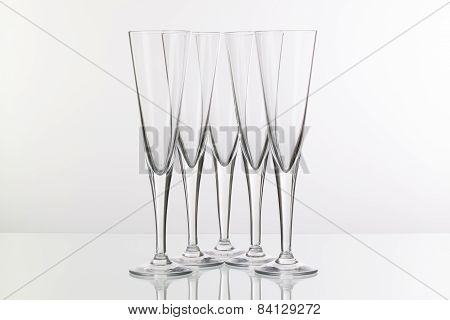 Five Champagne Glasses On A Glass Desk