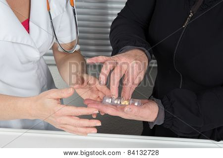 Friendly doctor giving medicine to an old woman