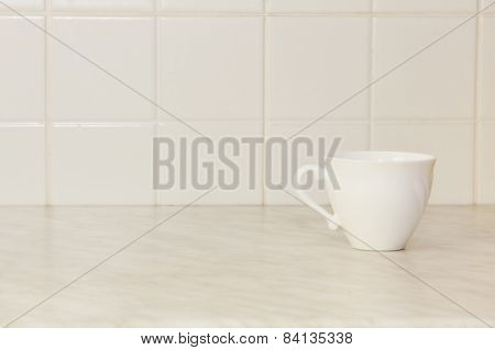 Ceramic tea cup on white kitchen table.