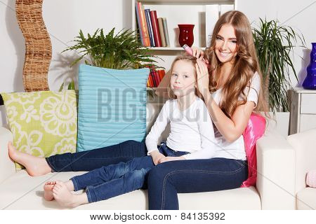 Happy Woman Combing Child's Hair