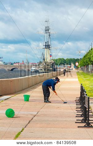 Cleaning woman washes the embankment of Neva River, St. Petersburg, Russia