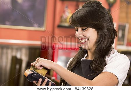 beautiful young waitress swiping credit card