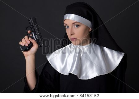 Portrait Of Young Woman Nun With Gun Over Grey