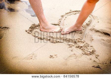 Couple's legs on beach sand