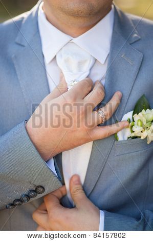 hands of groom in blue suit tying the necktie. unrecognizable man.