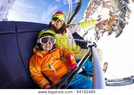 Happy boy with mother on ski chair lift