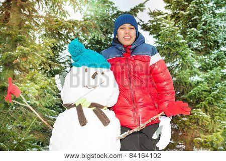 Arabian boy standing near snowman in winter