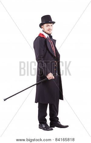Retro fashion man with beard wearing black suit. Holding a walking stick. Isolated in white backgrou