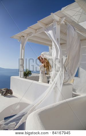 Beautiful bride in a wedding dress in greece with a long veil
