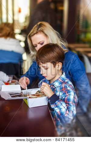 Little Boy Eating Salad With Mother