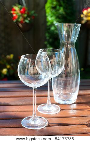 Two Transparent Shiny Empty Wineglasses And Carafe In Rays Of Sunlight.