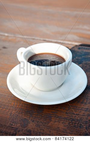 White Porcelain Cup Of Black Coffee On Wooden Table. Outdoors Closeup.