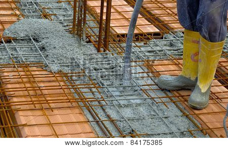Construction worker compacting liquid cement in reinforcement form