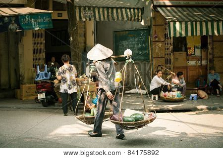 Woman vendor carrying baskets, Hanoi
