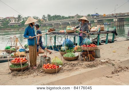Women in conical hat unloading boat,  Hoi An, Vietnam.