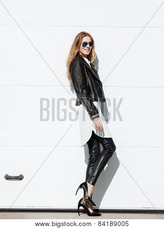 Young beautiful fashionable woman in leather jacket and high heels