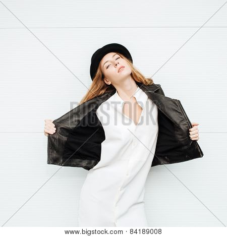 Young beautiful fashionable woman in leather jacket and  hat