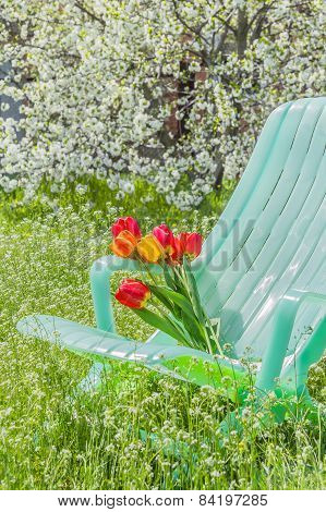 Deckchair And A Bouquet Of Tulips In The Garden