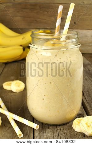 Banana smoothie in a jar on wood