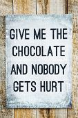 stock photo of hurt  - Hipster motivational wooden sign on rustic palette Give me the Chocolate and Nobody gets hurt - JPG