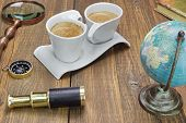 image of spyglass  - Earth Globe Vintage Spyglass Magnifying Glass Compass Two Notebooks Smoking Pipe and Two Espresso Coffee Cups On The Grunge Wooden Table - JPG