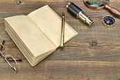 stock photo of spyglass  - Open Vintage Notebook With Blank Pages Gold Fountain Pen Glasses Retro Magnifier Compass and Spyglass On Grunge Woodeen Table Background - JPG