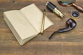 picture of spyglass  - Open Vintage Notebook With Blank Pages Gold Fountain Pen Retro Magnifier Compass and Spyglass On Grunge Woodeen Table Background - JPG