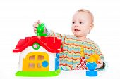 picture of cute innocent  - Cute baby play with toy house on white backdrop - JPG