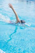 stock photo of goggles  - Young girl in goggles and cap swimming front crawl stroke style in the blue water pool - JPG