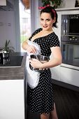 stock photo of pinafore  - the housewife in pin up style cooking meal - JPG