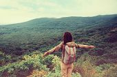stock photo of mountain-high  - Freedom traveler woman standing with raised arms and enjoying a beautiful nature - JPG