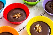 stock photo of truffle  - Chocolate Truffles in Colorful Cups on White Wooden Table