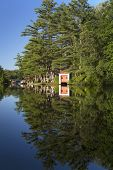 stock photo of pontoon boat  - Boat house and various buildings and boats on a river in New Hampshire in late day sun - JPG