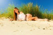 foto of dune grass  - Young woman female model in full length posing outdoor on background of dunes sky and grass - JPG