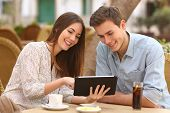 stock photo of married couple  - Happy couple watching media in a tablet in a restaurant terrace - JPG