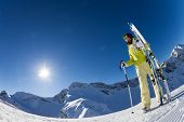 picture of caucus  - Fisheye view of woman standing and holding ski and ski poles during sunny winter day on Krasnaya polyana ski resort and Caucasus mountains in Sochi - JPG