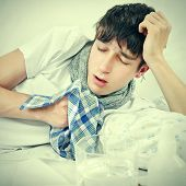 picture of sneezing  - Toned Photo of Sick Young Man is Sneezing on the Bed with Handkerchief - JPG