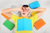 picture of yawn  - Tired Teenager Yawn with a Books on the Bed - JPG