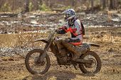 picture of motocross  - Motocross driver on muddy offroad track and wet terrain at cross country competition in Parola Finland - JPG