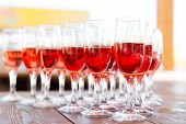 stock photo of champagne glasses  - Party row of red pink champagne glasses on a table - JPG