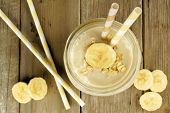 stock photo of masonic  - Banana oatmeal breakfast smoothie in mason jar with straws on wood table above view - JPG