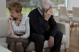 picture of conflict couple  - Offended elder couple sitting on the sofa - JPG