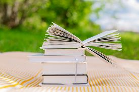 foto of piles  - pile of books with one opened book on nature background - JPG