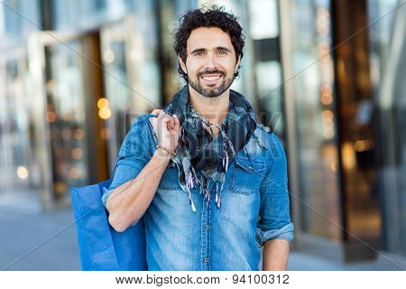 Handsome man with shopping bags walking outdoors