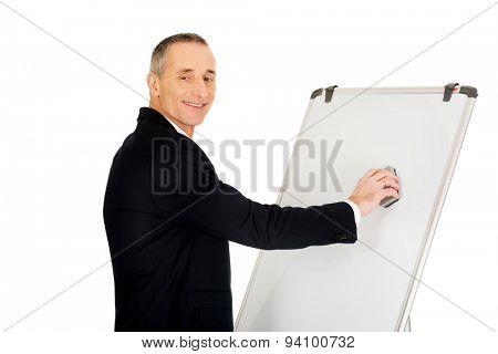 Mature businessman cleaning a flip chart.
