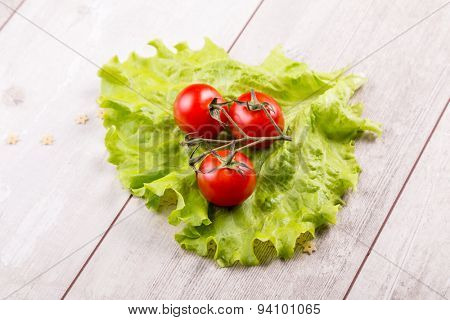 Tomato and green salad on wood background.
