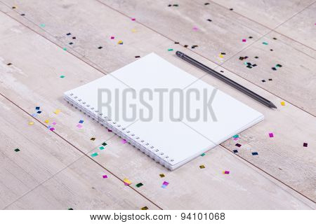 Blank notepad and pencil on the wooden table. View from above